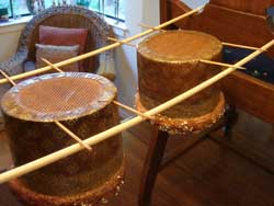 panettone hanging from dowels suspended between chairs