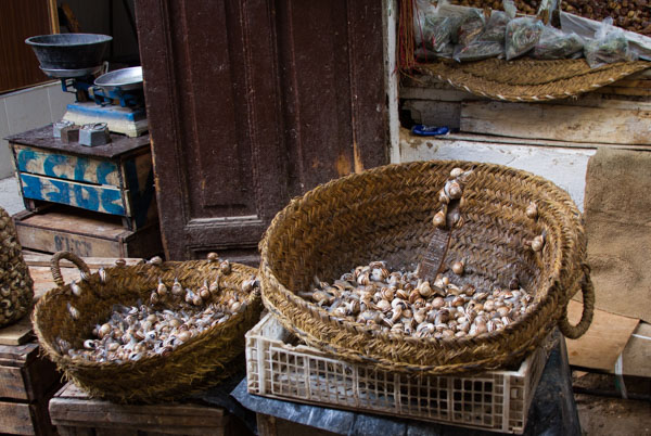snails are sold by weight; note the balance scale in the background